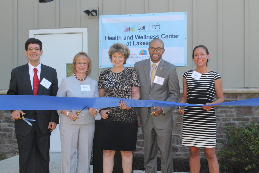 five Bancroft board members stand holding a blue ribbon and large scissors outside of the new Health and Wellness Center at Lakeside building