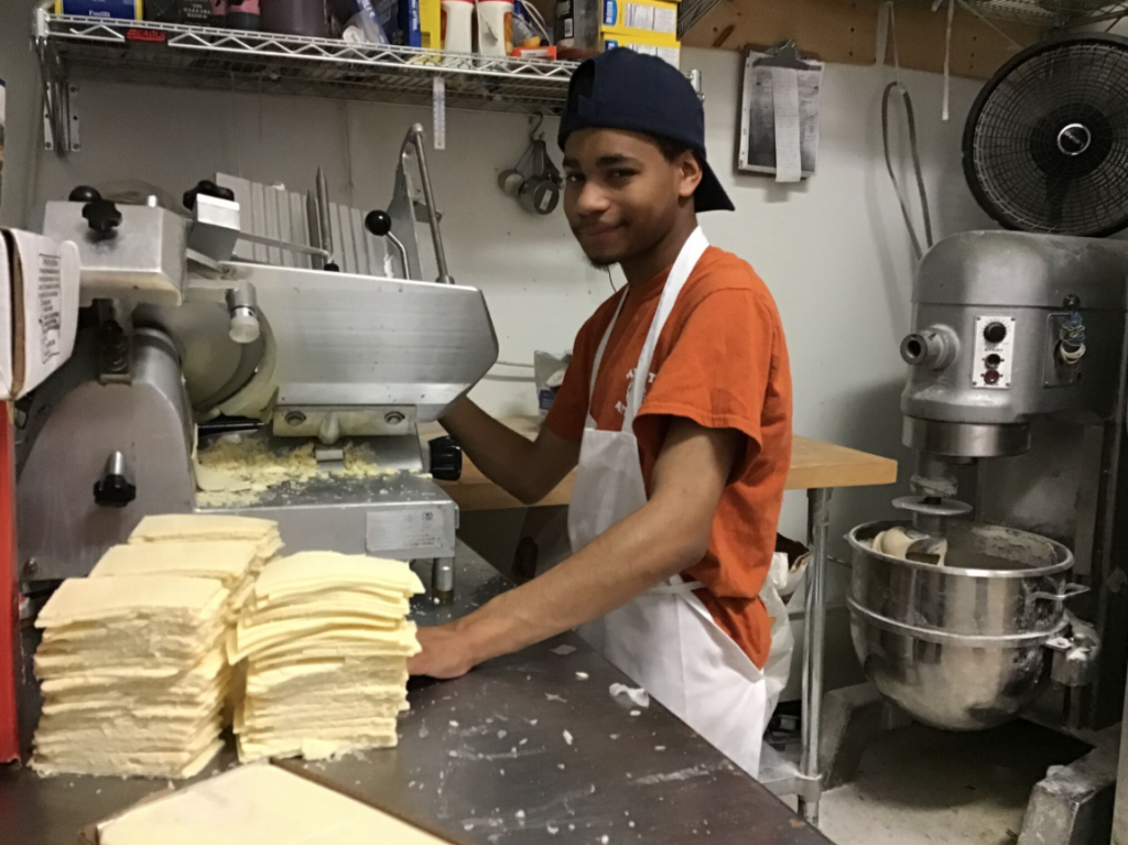 A young adult male is using a deli slicer to slice american cheese.