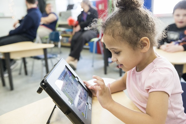 Young student sitting at desk using assistive technology ipad
