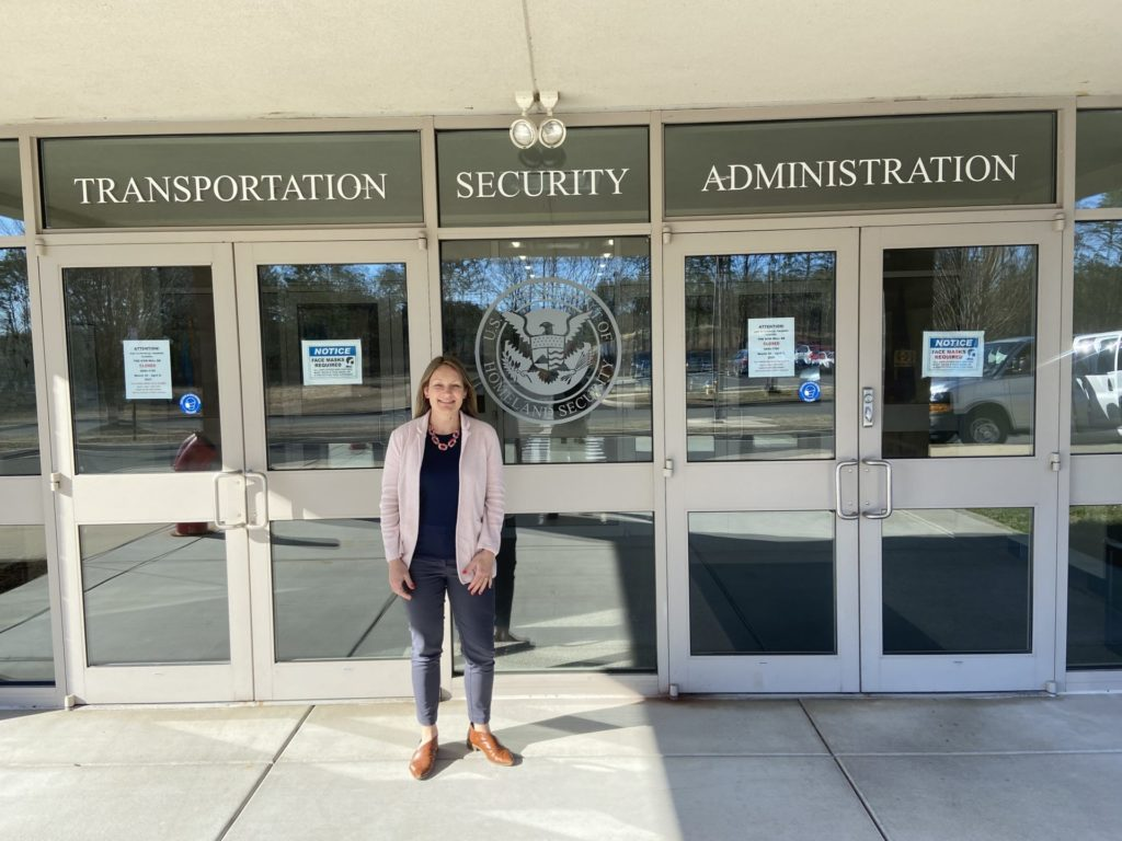 """a light-skinned woman with blonde hair wearing a pink suit jacket and blue pants stands in front a building with the sign """"Transportation Security Administration"""""""